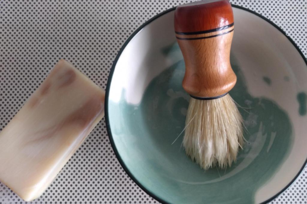 Scheerzeep en scheerkwast in bakje om scheerschuim mee op te kloppen.